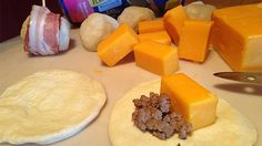 Cooked ground bee3 and cheddar cheese on a round of biscuit dough