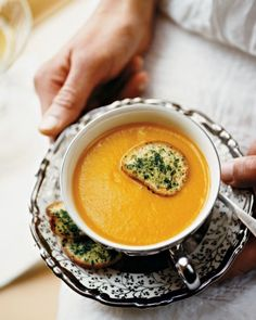 This delicious pureed soup gets loads of flavor and texture from winter squash and potatoes. Use buttercup, butternut, Hubbard, or kabocha squash in this recipe. The crostini garnish is brushed with cream that has been infused with chopped rosemary, parsley, and thyme, then broiled until crisp. The soup and crostini can be made up to two days before Thanksgiving.