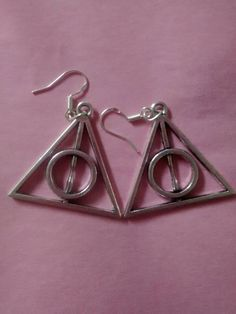 These earrings have personally been made by myself. They consist of a sterling silver hook with a Deathly Hallows charm hanging from each.
