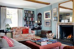 Farmhouse Living Room with Kilim-covered sofa in Living Room Ideas. Blue living room with inbuilt bookshelves, ottoman coffee table and fireplace. Country style on House.