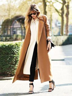Caramel colored coat paired with a calf length beige button down dress, black skinny jeans, and black heeled sandals.