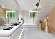 Soft tones and metallic details feature across the two floors of this London boutique created by Universal Design Studio for fashion brand J&M Davidson