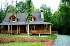 I love the wrap around porch and the simple charm of this log home.