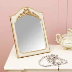 This beautiful framed mirror will sit perfectly on a dressing table, mantel piece or windowsill. Finished in shades of pale green and vintage gold, the frame will add a touch of colour to wherever it is placed. To the top of the frame, there is a decorative flowing ribbon ornament, creating a stunning finishing touch to the mirror while the outside of the frame is decorated with beaded piping adding extra texture!