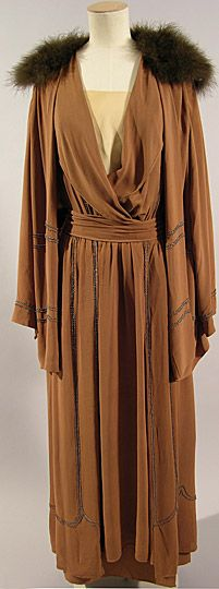 This suit designed in circa 1915-1920 was worn by Maud Messel. The dress is made of brown silk georgette, trimmed with rows of glass beads. It has a low v-shaped cross-over neckline with turned back lapels, full length sleeves and a long gathered skirt with a tie belt. Under the dress was worn a grey silk and brown chiffon slip. The matching jacket has a collar of swansdown. The suit is an example of Maud Messel's fashionable daywear of the mid-late 1910s. This suit is part of the Messel…