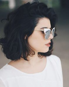 acconciature-capelli-corti-carré-sopra-spalle-ondulato-voluminoso-tinta-nera-occhiali-sole-montatura-dorata