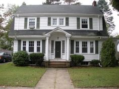 Dutch Colonial - roof, siding arched top over entry way symmetrical.