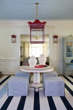 Make an Entrance. Red lantern pendant and sconces, white center table, and black and white striped rug. Interior Design: Tobi Fairley.
