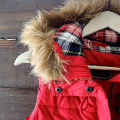 vibrant red toned puffer vest featuring a contrasting plaid lining and removable hood fur outer lining.