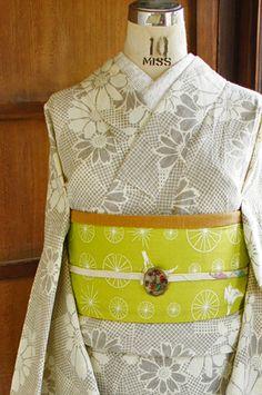生成り色と淡く優しいブラウンで染めだされた格子を重ねたようなデザインに雛菊のような愛らしいお花が散らされたナチュラルモダンな浴衣です。