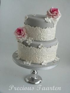Wedding or birthday two-their cake. Silver and white lace with pink accent flower and beads