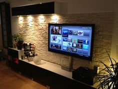 Entertainment center with cement stone wall behind it.  Replicate with Brick for a faux loft feel?