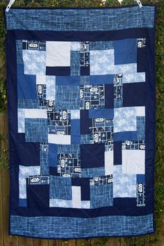 This quilt is a handmade, lap quilt that is made with different fabrics that are pictured above in navy fabrics with a star wars fabric. The