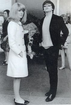 """French film star Catherine Deneuve, here seen with her husband, British fashion photographer David Bailey, wears a 1966 white trapeze line coat."""""""