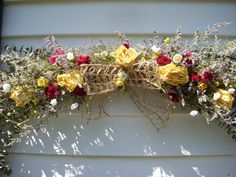 Victorian eucalyptus swag with dried herbs and roses and a wispy burlap bow