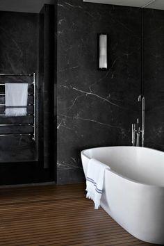 salle de bain mur en marbre noir, baignoire blanche sol en parquet bois foncé