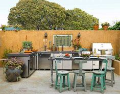 outdoor kitchen with stainless steel appliances and blue wooden chairs