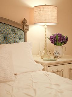 Great tufted headboard;  beautiful, simply styled bedside table; love the lampshade, clock and flowers.  Serene.