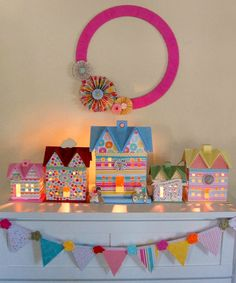 Colorful cardboard houses. Covered in scrapbook paper. So cute for Christmas, or for the girls room.