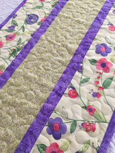 Whimsical, Spring Table Runner Quilt featuring smiling snails, grasshoppers and lady bugs. Green, purple and pink are among the colors that make up this delightful table runner. Charming on your kitchen table...or where ever you want a touch of sunshine and happiness!  Measures approximately 15 W x 48 1/2L.  I have free motion quilted a meandering stitch. Warm and Natural batting is sandwiched in between layers. Matching print binding has been doubled and machine stitched to quilt. Rever...