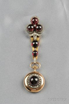 Antique Garnet and Diamond Pendant Watch, the watch pin designed as a clover of garnet cabochons and rose-cut diamond accents, and suspending a conforming pendant watch with white enamel dial and Roman numeral indicators, silver and gold mount, total lg. 3 1/2 in., (bezel around dial is not gold). Victorian or Victorian style