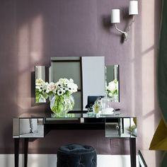 Mirrored bedroom dressing table-- Deep plum walls create a glamorous feel, while mirrored furniture lifts the look and allows light to reflect around the room. Use a George Smith buttoned velvet footstool for added opulence.