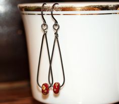 AJE Earring Challenge Wk 37/52 – For this pair of earrings, I used a lovely pair of shiny, red lampwork beads made by pinocean (Mika Collins), suspended from 20 gauge, dark annealed, steel wire teardrops.