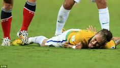 Down: Neymar lies on the floor in pain and holds his back...
