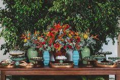 Mesa de doces rústica com arranjos vermelho, laranja e amarelo com vasos turquesa. Elegante e fino. Foto: Tempo Digital