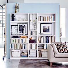 Bibliothèques BILLY blanches remplies de livres, photos et objets personnels. Dans le bas, des paniers de rangement.