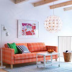 """Ein Wohnzimmer mit KARLSTAD 3er-Sofa mit Bezug """"Husie"""" in Orange, IKEA PS 2012 Couchtisch in Weiß und MASKROS Hängeleuchte"""