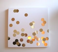 Get some metallic gold cardstock and glitter paper from Joann's and used my 2-inch circle punch to create the confetti.  Place it haphazardly around the white canvas and secure it with spray adhesive.