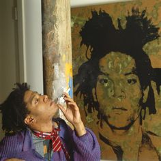 Jean-Michel Basquiat in his Great Jones Street studio, in front of a piss painting of himself by Andy Warhol.Photo by Tseng Kwong Chi, 1987.