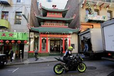 In this Wednesday, Dec. 16, 2015 photo, people make their way past a Chinatown bank in San Francisco. The best plan for tackling San Francisco's Chinatown is no plan at all. Simply wandering the wide streets and narrow alleys will take you where you need to go. Photo: Eric Risberg, AP / AP