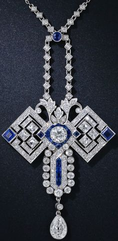 "Art Deco Diamond and Sapphire Butterfly Pendant Necklace, circa 1920s. The ""wings"" are comprised of 6radiant and sizable French-cut diamonds and a pair of square sapphires. The head centers on a bright European-cut diamond framed in electric blue calibre sapphires, and the abdomen features a center row of calibre sapphires framed by diamonds. An old mine pear shape diamond dangles below. 4.50 carats total diamond weight. An applied plaque on the reverse  reads ""K.A.H - A.E.H. 1865-1915""."