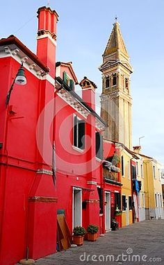 Photo taken on the island of Burano in the village of fishermen and lace embroiderers in the municipality of Venice Italy. In the image we see in the foreground of a red house with a tall, lit fireplace particular, further and above other houses Stands Tall on the cathedral bell tower.