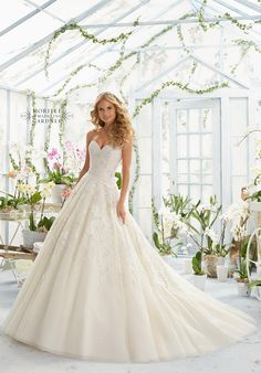 PEARL AND CRYSTAL BEADING ON ELEGANT EMBROIDERY THAT DECORATES THE CLASSIC TULLE…