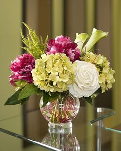 Fuchsia pink peonies, green hydrangeas, cream roses and soft green calla lily buds are nestled amongst a swirl of fuchsia pink florist wire. Designed in a glass ball with our crystal clear acrylic water.