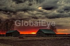 Two Old Barn Houses In The Springtime Sunset. The sun sets late in the spring nights and colors the barns and the fields beautifully. The summer is almost here in the Northern Finland.Stock Photo By Jukka   Heinovirta