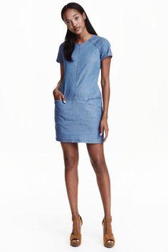 Vestido curto: Vestido curto em tecido macio de viscose e algodão com aparência de ganga. Tem mangas curtas raglan com dobra cosida na extremidade, corte ao nível da anca, bolsos na frente e fecho éclair oculto atrás.