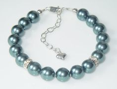 Swarovski 8mm Tahitian crystal pearls combined with 2 crystal /silver rondelles to add some subtle bling! Tahitian is a beautiful dark green/gray color.  Bracelet size is 6.5, plus a 2 sterling silver extension chain. Fully extended, its 8.5 and should fit most people. If youd like it a bit shorter or longer, just let me know.  Made with sterling silver lobster clasp and sterling silver components. All crystal beads and pearls are genuine Swarovski crystals.  Perfect for the holidays and New…