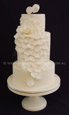 Four-tiered ivory wedding cake with cornelli fine piping in royal icing and 'exploded rose' design. By Sweet Perfection.