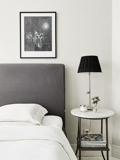 Gray headboard with small side table, black and white art, and black table lamp