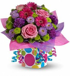 Teleflora's Confetti Present  :-Flowers and presents make festive gifts, especially when they are paired together!  This happy bouquet includes pink roses, hot pink miniature gerberas, purple carnations and matsumoto asters and green button spray chrysanthemums accented with fresh greenery. The bouquet is delivered in a festive gift box accented with hot pink and purple water-resistant tissue paper and pink, green and blue ribbon streamers for a truly unique birthday gift.
