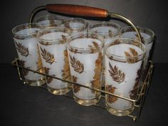 My grandmother had these. Set of 8 Mad Men era glasses in holder, Libbey Starlyte Gold, I recently was able to pick up a set at an estate auction, just to remind me of my grandma. Love them.