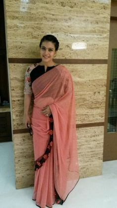 Kajol in peach saree paired with black blouse with floral sleevs