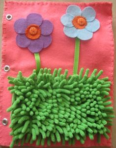 Flowers attached with buttons and fuzzy grass quiet book page.