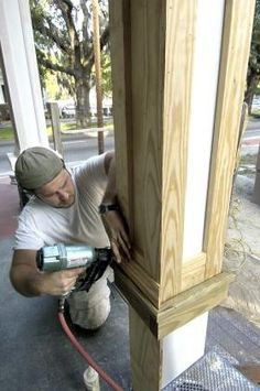 Carpenter Zac Curl attaches trim to the pillars that support the Tison House front porch.