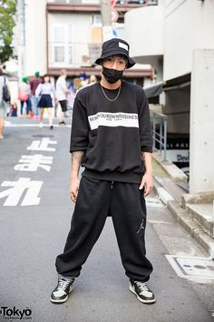 Tattooed and pierced 666Dievil666 on the street in Harajuku wearing a bucket hat and sweatshirt from the Japanese brand M.Y.O.B NYC with a mask, Nike sweat pants, and Nike sneakers. His accessories are from Oz Abstract Tokyo.