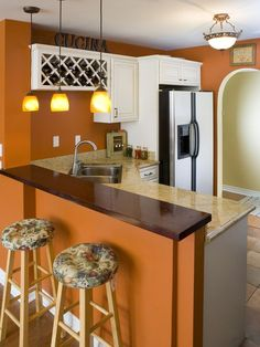 Glossy white cabinets stand out against the pumpkin-orange walls. Design by Erica Islas.